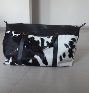 Black and white cowhide duffel bags