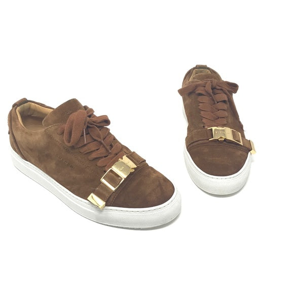 Buscemi buckled calf suede low-top Sneaker in tan. Consists of a 1 inch sole with a round toe and golden buckle. Lace up front with an embossed logo on the side and the tongue. Rubber outsole. Faint signs of wear on the soles and light fading on the suede.  Size: EU 43  Made in Italy.