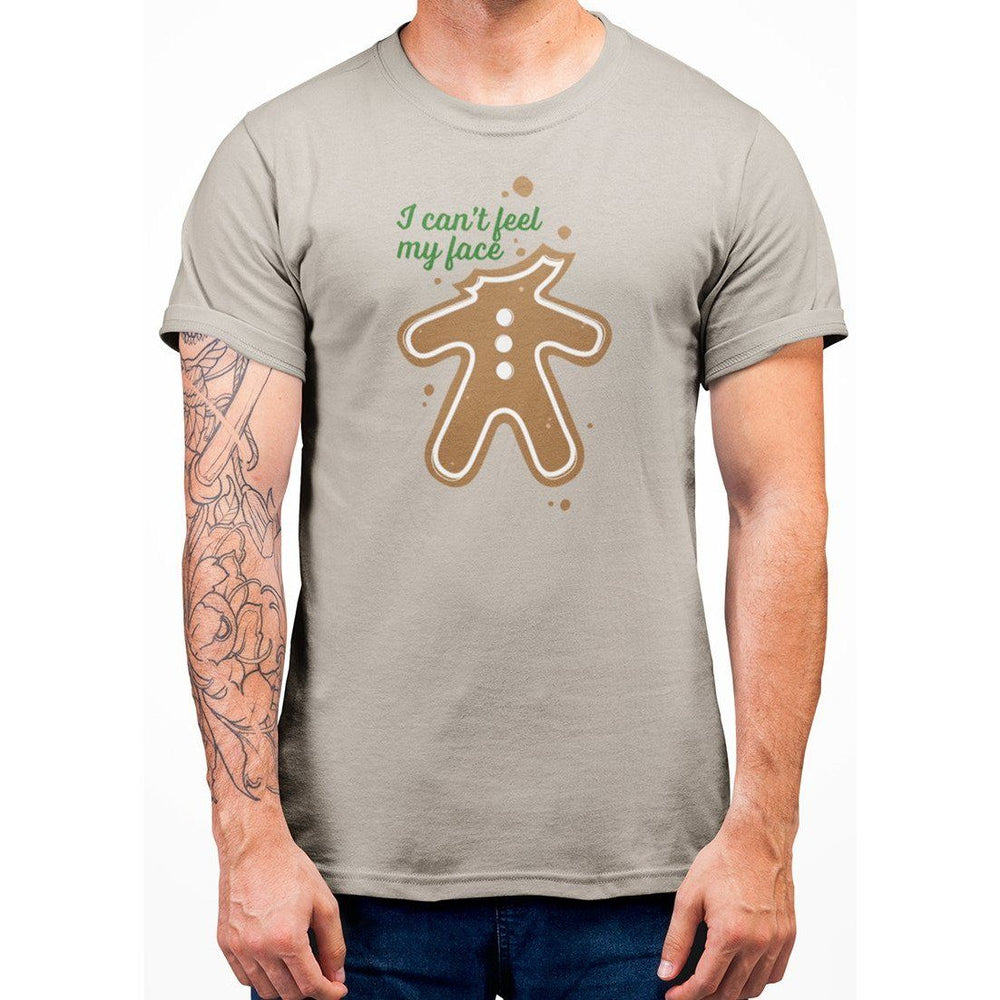 Sand color t-shirt with green text I Can't Feel My Face and image of ginger bread with no head