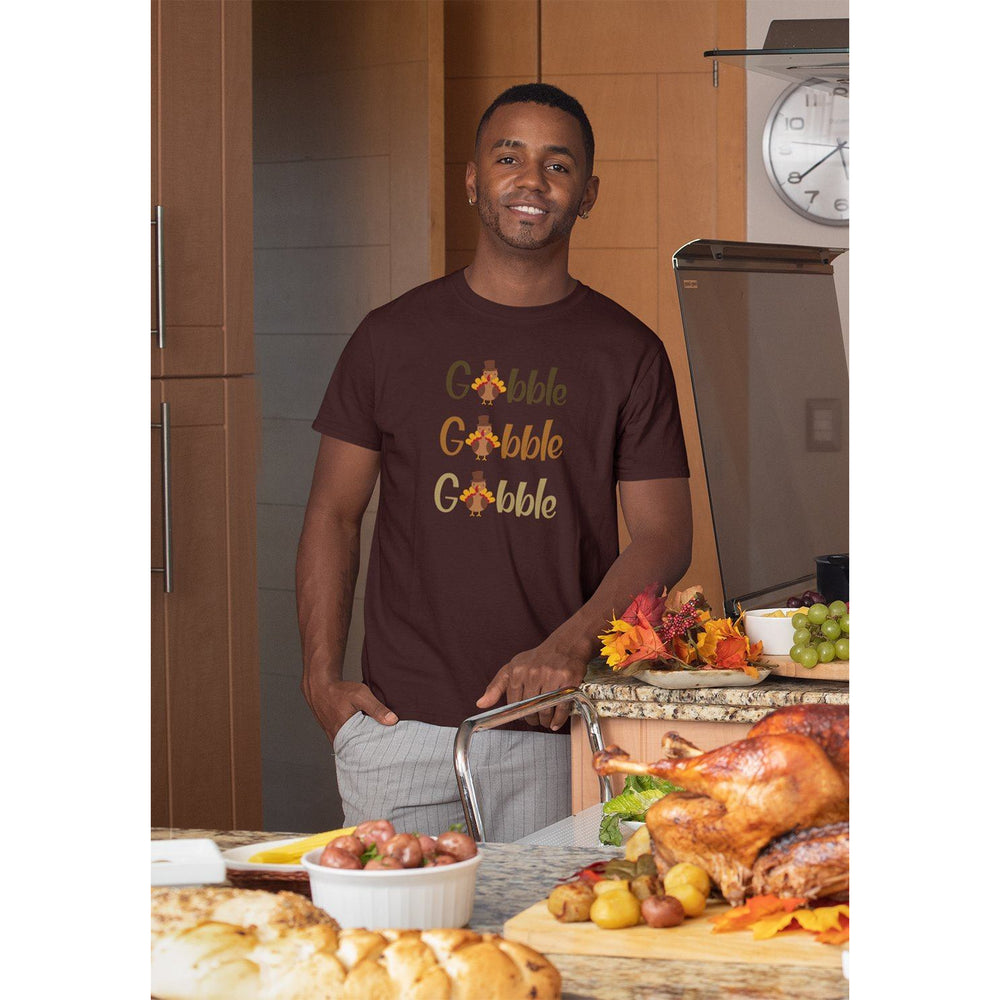 Madn wearing a maroon t-shirt that says gobble gobble gobble in front of a turkey