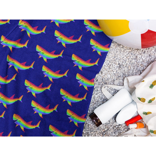 Dark purple beach towel with rainbow sharks on it on the beach