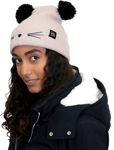 A model wearing a beige fashion beanie with two pom-poms on top with black whiskers in front