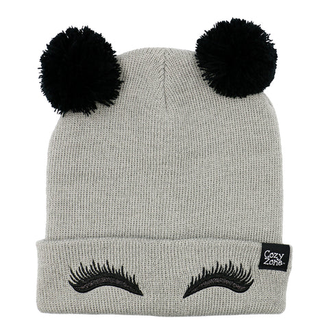 A grey fashion beanie with two pom-poms on top with black eyelashes in front