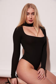 A soft, stretchy, ribbed, effortless long-sleeve bodysuit with a deconstructed turtleneck. Button closure in back. You'll feel the quality on this one. Soft to skin, sexy to eyes. Dress it up or wear it for your next date night.