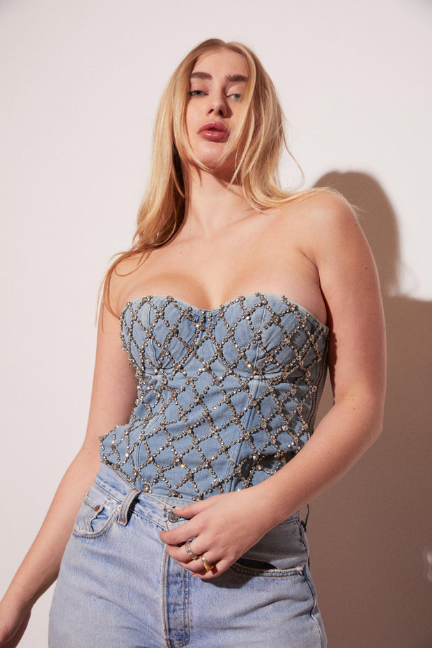 Shine bright like a diamond. This structured, crystallized denim bustier is the bold style move you have been waiting for. Denim blend corset, rhinestone detail, and wide silk ribbon tie-up detail in the back and side zipper detail. Style it with jeans and give Britney and Justin '00 a run for their money.