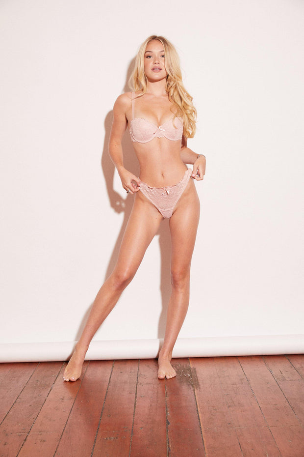 a soft, lustrous, effortlessly sexy, lace bra and panty set. Pink padded bra complete with underwire cups, hook-and-eye closures, and adjustable straps. Set with thong panty.