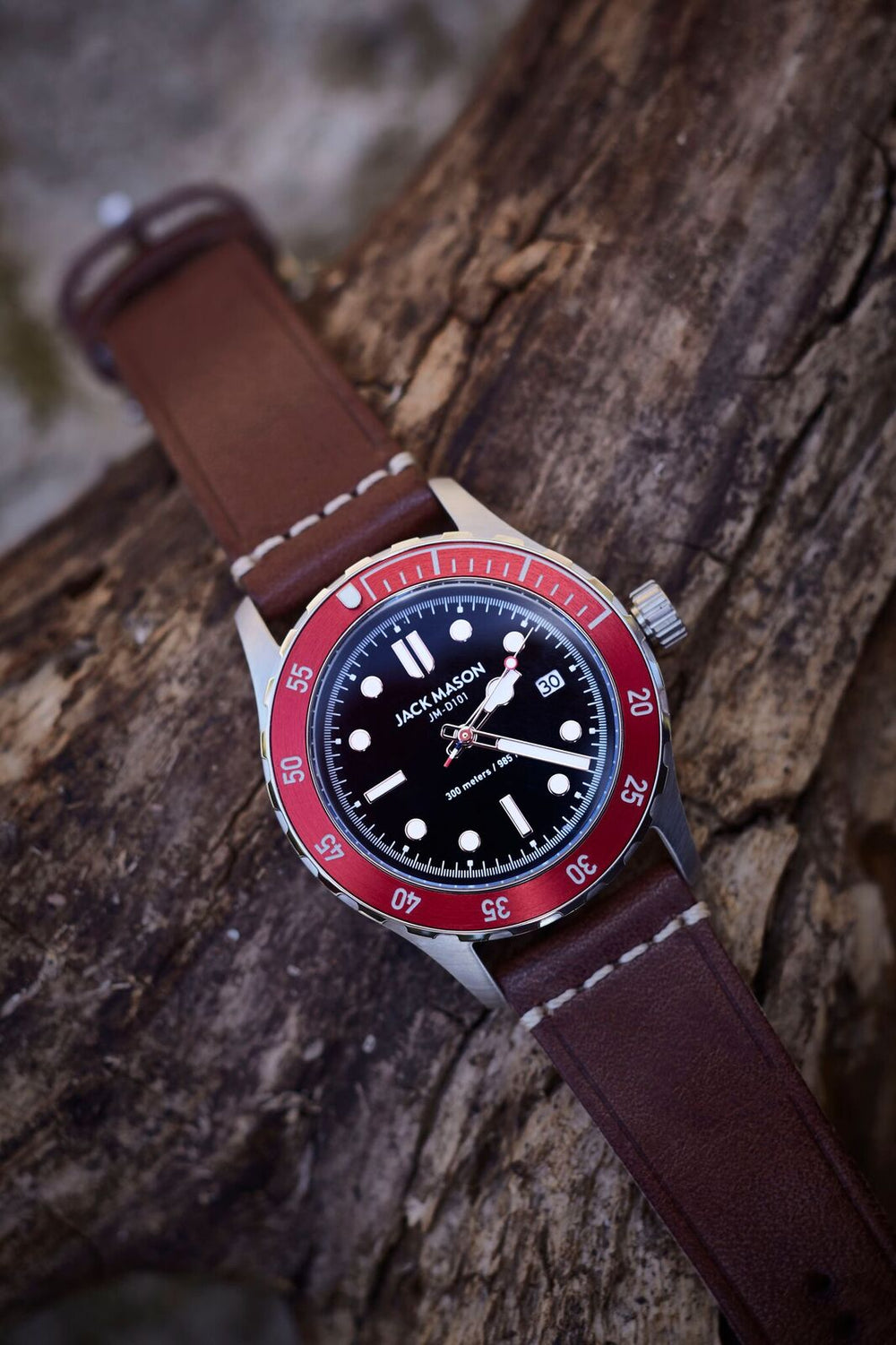 The black, red, and steel diver watch with brown leather watch strap