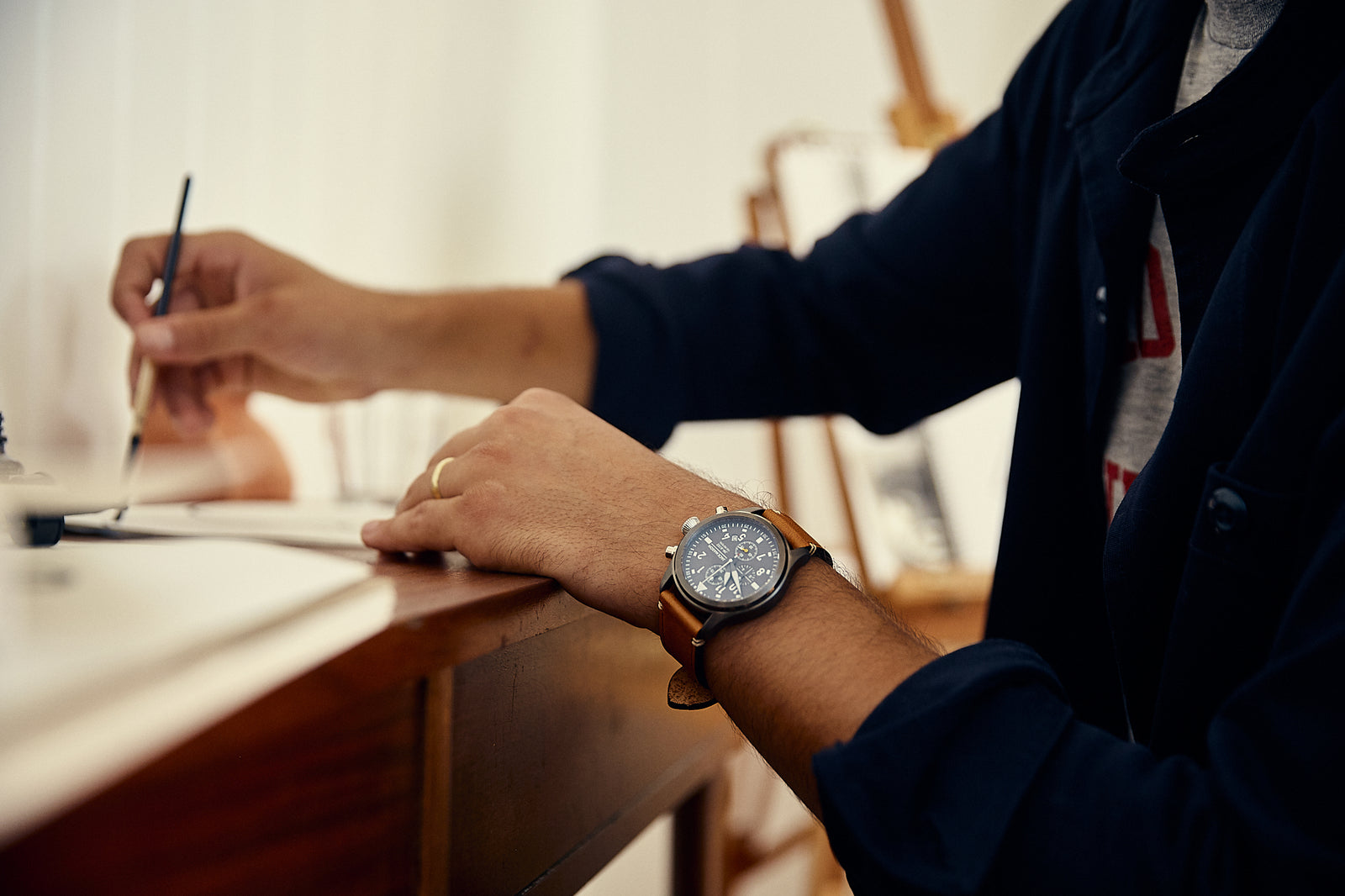 A man writing while wearing the chic aviator chronograph watch from Jack Mason