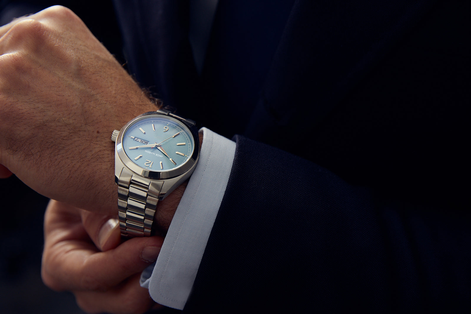 A man in a nice suite wearing the Canton Day-Date Automatic watch with a light blue dial