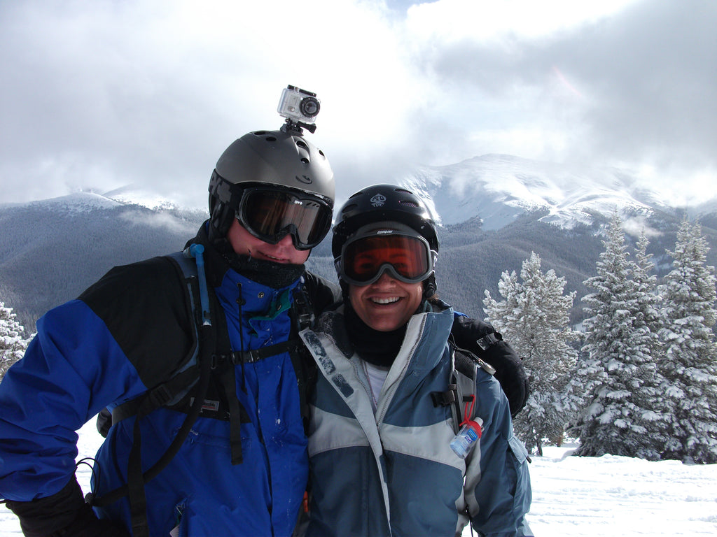 Founders, Lonnie and Melissa, wearing snowboard gear and winter apparel with snow covered mountains behind them.