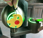 Load image into Gallery viewer, Simba Magic Band Buddy scanning into park kiosk with green ring lighting up