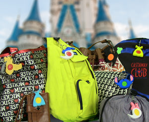 Many different Magic Band Buddies shown attached to various bags and backpacks