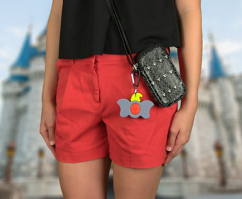 Girl using Dumbo Magic Band Buddy with a carabiner clipped to a pouch / purse