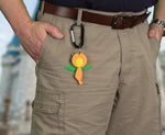 Load image into Gallery viewer, Man with Orange Bird Magic Band Buddy attached to a belt loop with a carabiner