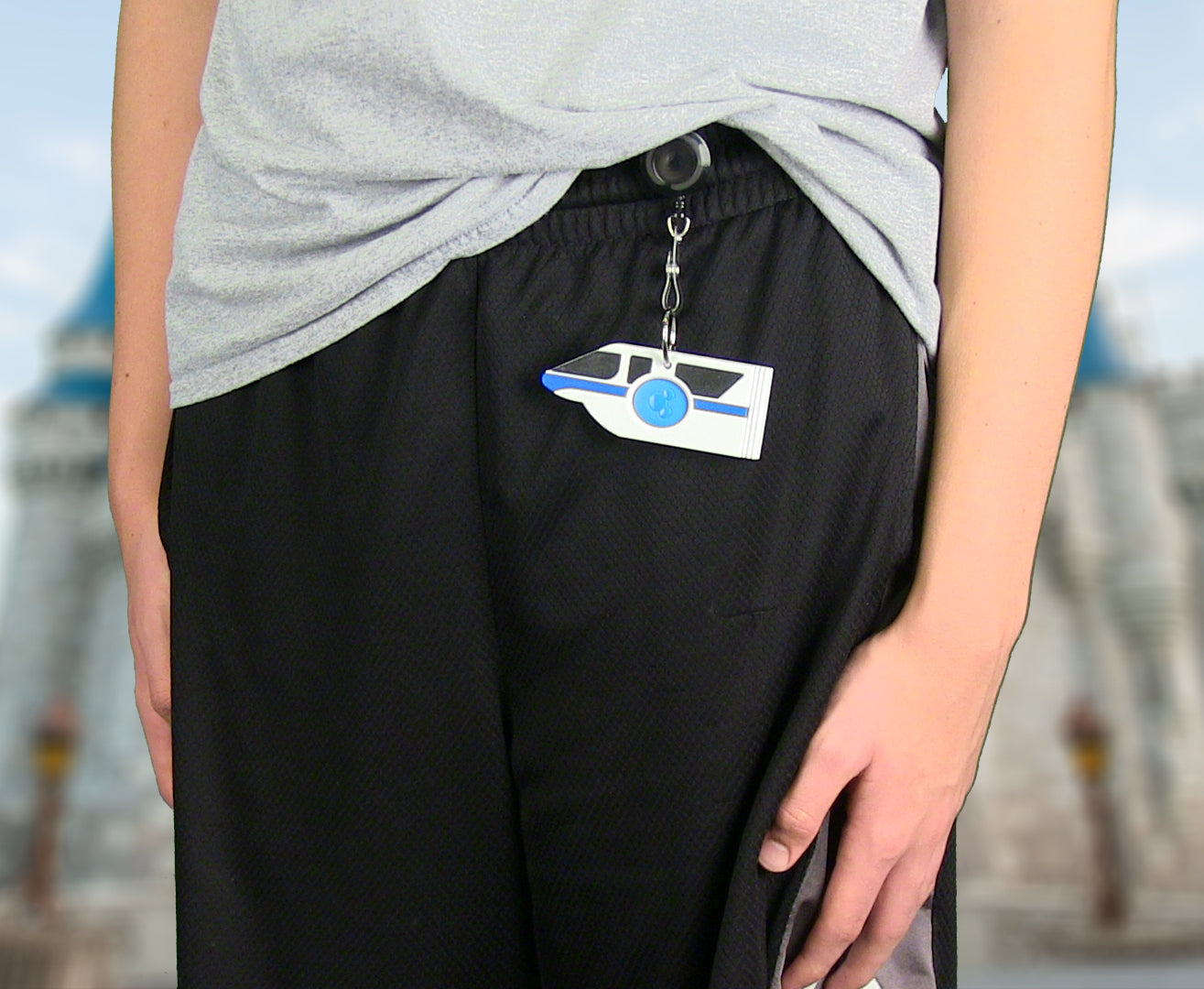 Boy using Monorail Magic Band Buddy with a retractable badge reel clipped to shorts