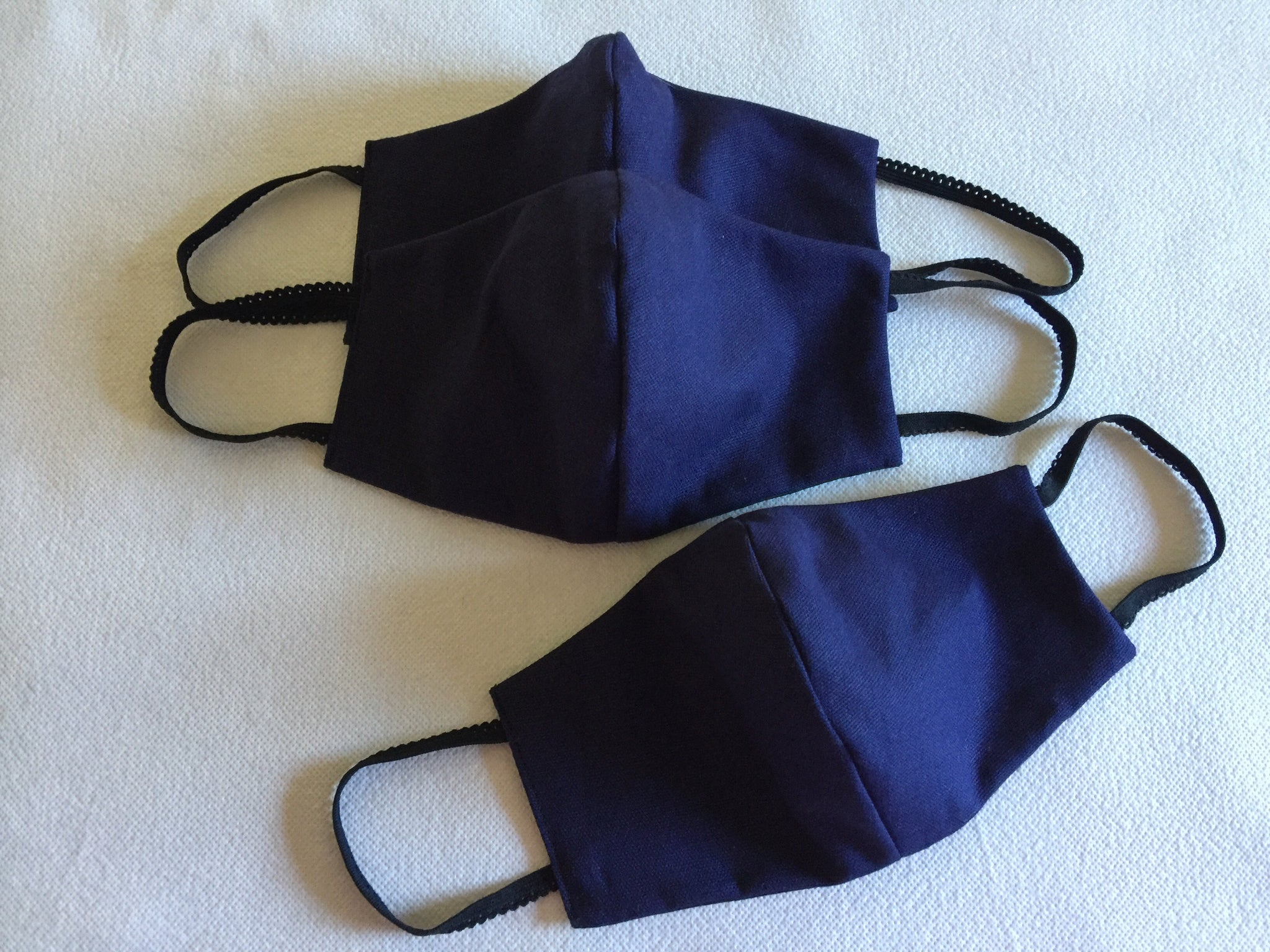 Face mask featuring navy linen with a black cotton reversable option .