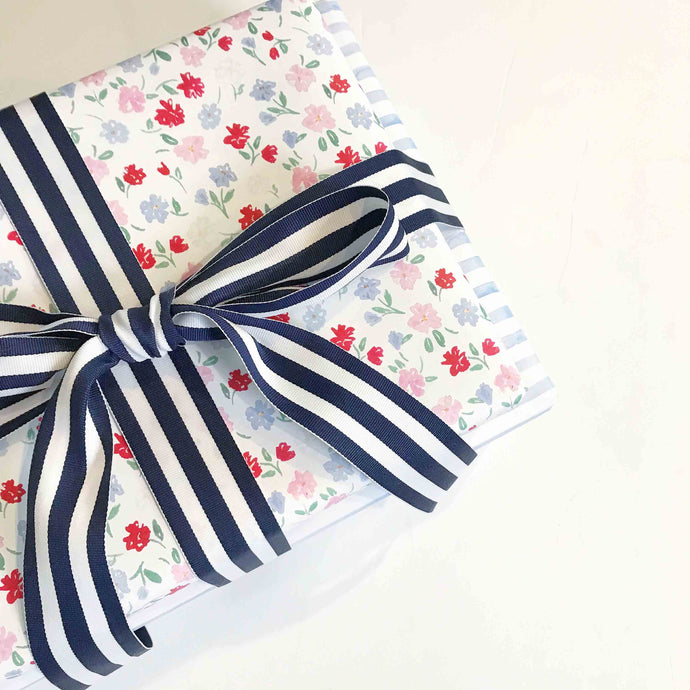 present wrapped in blue red and pink watercolor floral wrapping paper