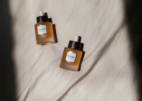 Organic Face Oil from La Coéss flat lay on white bedding