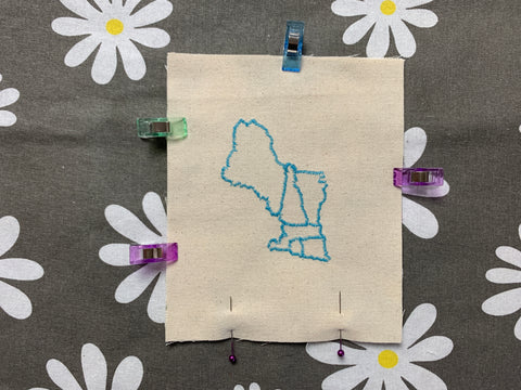 fabric scrap map piece clipped and pinned for sewing