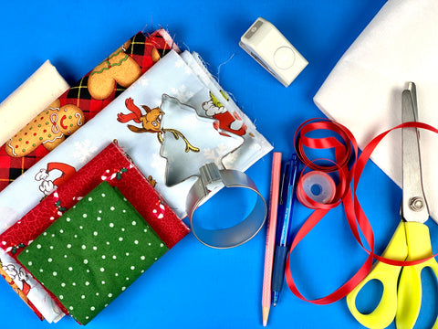 supplies for sewing project, motif fabric, ribbon, scissors, pencil, hole punch