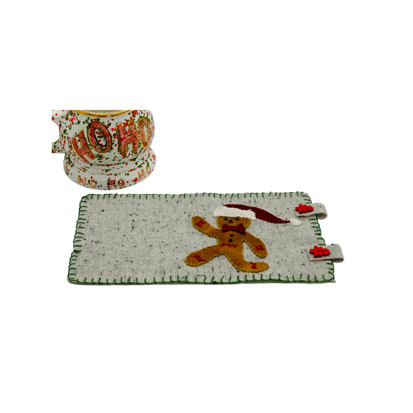 gingerbread person mug rug wool applique kit with christmas mug nearby.