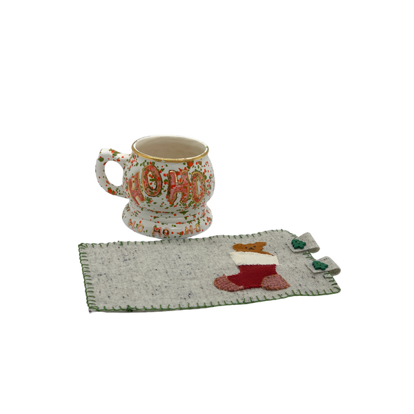 Wool applique mug rug with koala bear coming out of christmas stocking with tea cup nearby.