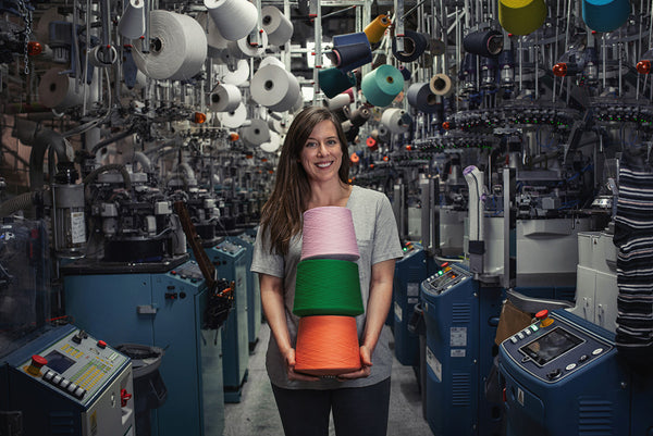 brunette woman smiling and holding colorful spools of yarn, standing beside knitting machines in a sock mill