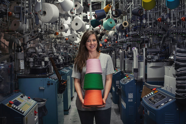 Smiling woman holding bright spools of organic cotton in a sock mill.