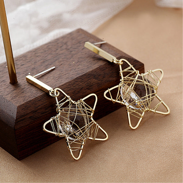 Metal bar with empty star shape with wound metal birds nest holding clear centre gem