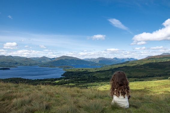 girl sitting in front of scotland lake and hills