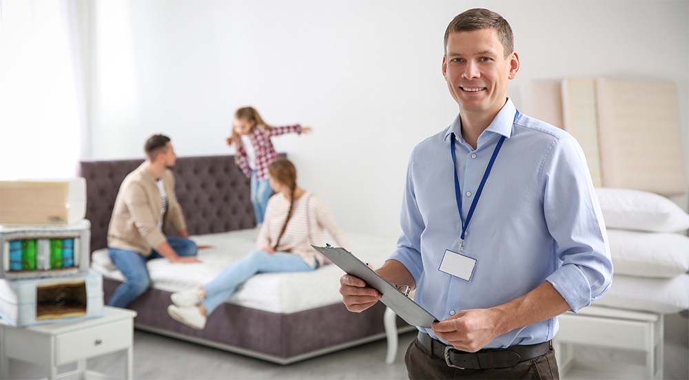 Happy salesman and his clients in mattress store