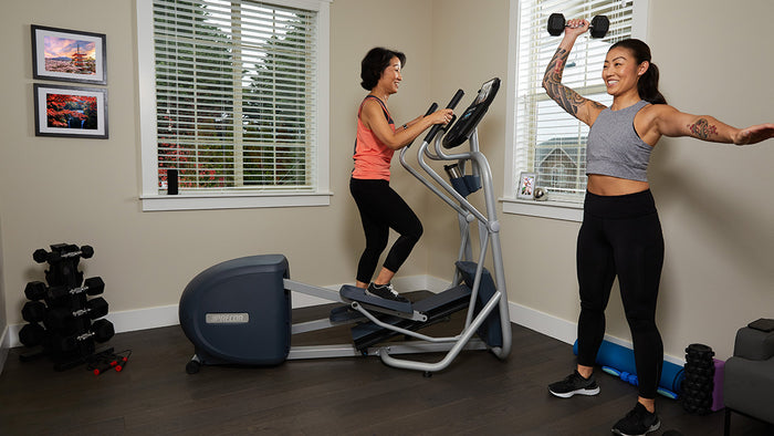 Two women working out at home, one is lifting a dumbbell over her head, the other is on a Precor elliptical
