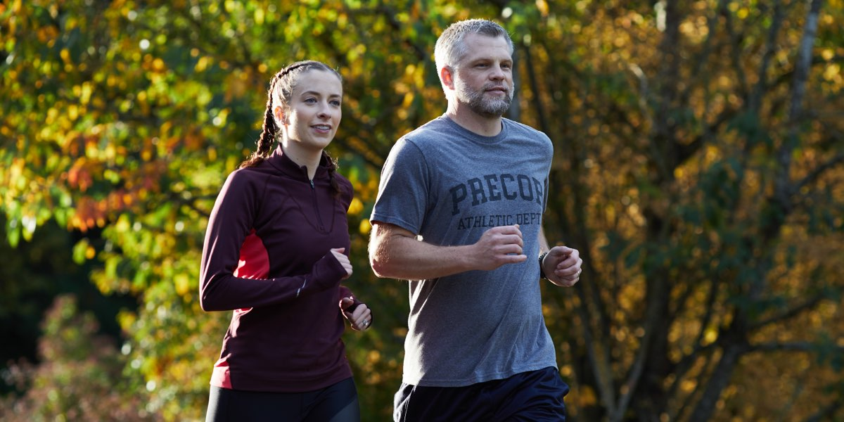 Man and woman running outside during the fall