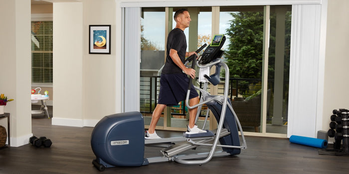 Man working out in his home gym on a Precor elliptical EFX 447