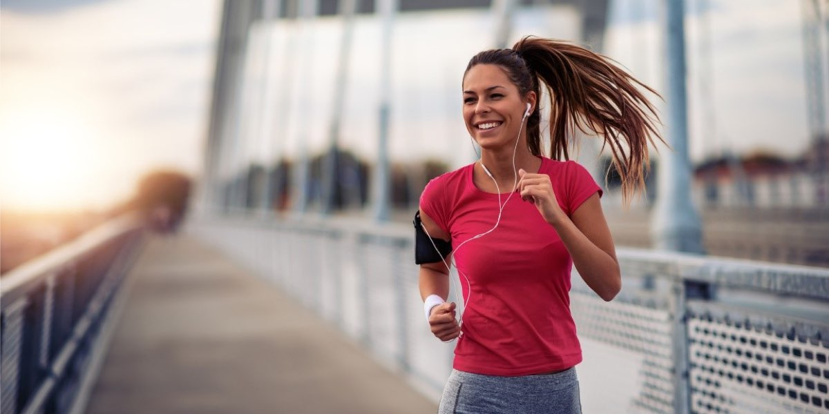 Happy female running outside over a bridge