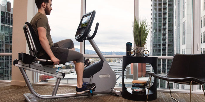 Man exercising on a Precor RBK 865 recumbent bike in his home gym