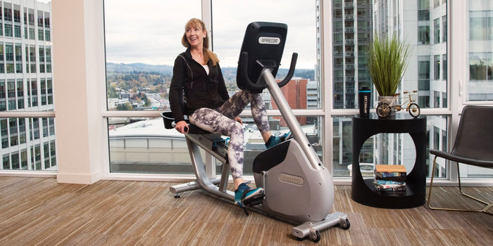 Woman working out in her home on a Precor recumbent bike RBK 885