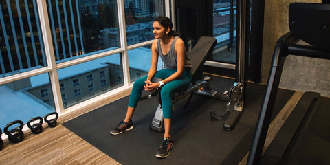 Female resting between sets in her home gym that features Precor DBR 119 adjustable bench, FTS Glide functional strength training system, and a Precor TRM treadmill