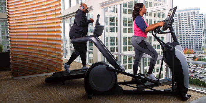 Male and female working out in their home gym on a Precor elliptical EFX 685 and a Precor treadmill TRM 681