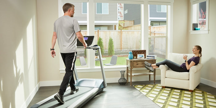 Male walking on his Precor treadmill TRM 211 in his home workout room while a woman hangs out in the chair talking to him