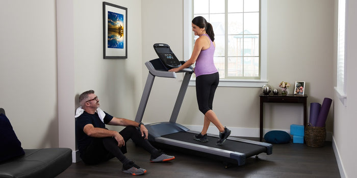 Woman walking on a Precor treadmill at home with her husband chilling on the floor post-workout