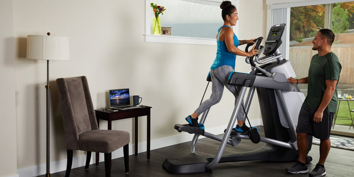 Female working out in her home gym on her Precor AMT 835 Adaptive Motion Trainer, while her husband looks on