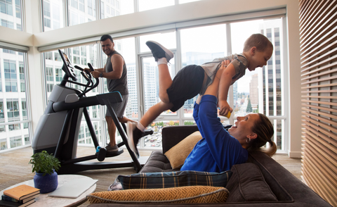 Mother holding up her son over head while dad looks on while he is working out on their Precor AMT 885 Adaptive Motion Trainer with P82 console