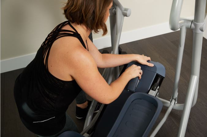 Close up image of a woman adjusting the manual incline of her Precor elliptical EFX 222