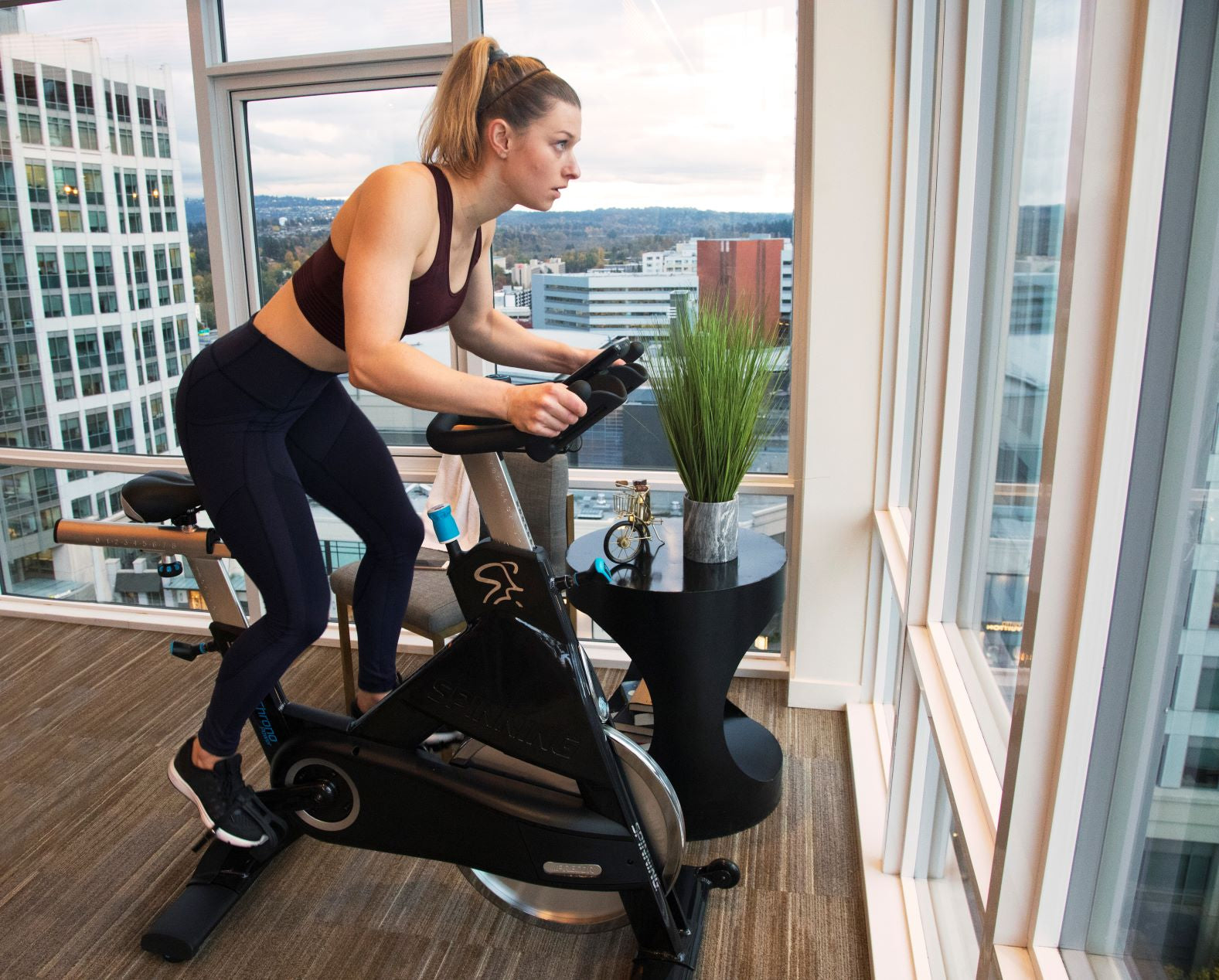 Female spinning on her Precor Spin bike at home