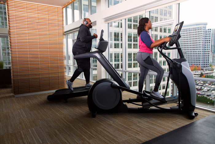 Man exercising on treadmill and woman working out on a Precor elliptical machine in a high-rise apartment building