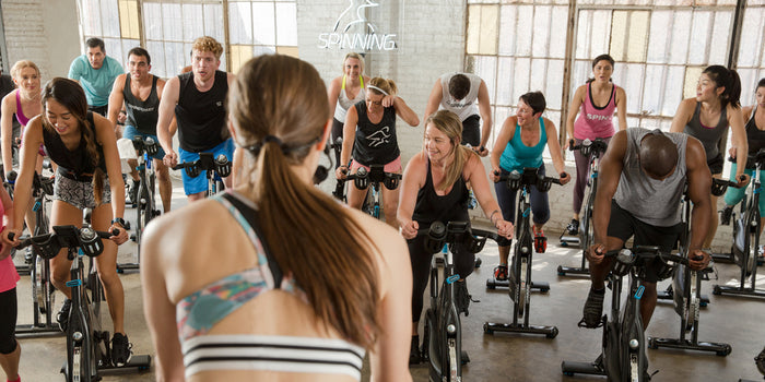 Group Spin Class from the view behind the instructor overlooking the group of exercisers on their Spinner bikes