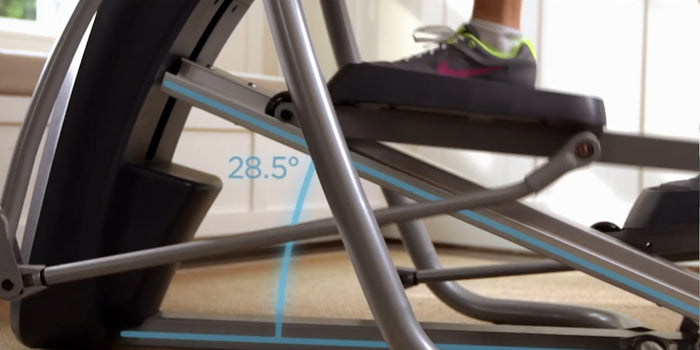 Close up of a Precor elliptical machine in use featuring its 28.5-degree adjustable incline
