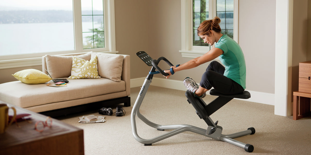 Female in her living room using the Precor 240i StretchTrainer