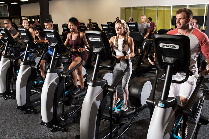 Precor professional elliptical fitness crosstrainer in a fitness center with exercisers working out
